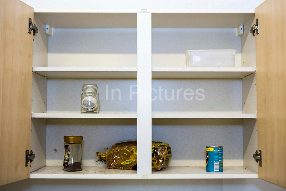 An almost empty food cupboard in a family home in Hackney, London, United Kingdom.  The family have recently been pushed into poverty by changes to the Government's welfare system and they now live below the poverty line, alongside an estimate 13 million other people in the UK.  The cupboard contains tea bags, coffee, baked beans and a loaf of bread.