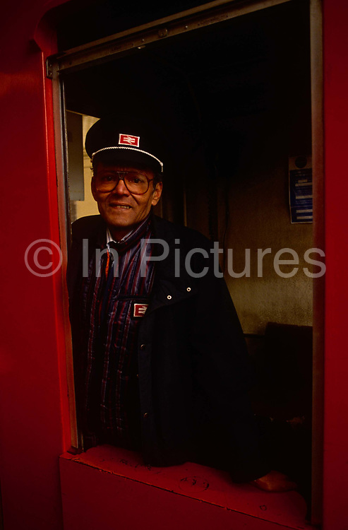 """A 1992 portrait of a British Rail employee stands at the gate of a platform at Victoria station. Wearing the old uniform of that rail company. British Railways (BR), which from 1965 traded as British Rail, was the operator of most of the rail transport in Great Britain between 1948 and 1997. It was formed from the nationalisation of the """"Big Four"""" British railway companies and lasted until the gradual privatisation of British Rail, in stages between 1994 and 1997. The British Rail """"double arrow"""" logo is formed of two interlocked arrows showing the direction of travel on a double track railway and was nicknamed """"the arrow of indecision"""". It is now employed as a generic symbol on street signs in Great Britain denoting railway stations."""