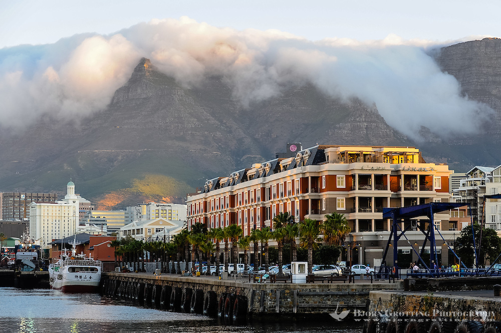 The Victoria & Alfred Waterfront in the harbour of Cape Town, South Africa. A common sight, fog flowing over Table Mountain.