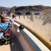Tourists overlook the Hoover Dam's massive concrete wall from a viewing platform at the top of the dam on the Nevada side. In the background can be seen a little of Lake Mead on the Colorado River.