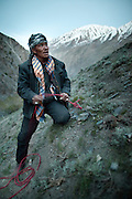 A Kyrgyz caravan leader attach his horse. Trekking up and along the Wakhan river, the only way to reach the high altitude Little Pamir plateau, home of the Afghan Kyrgyz community.