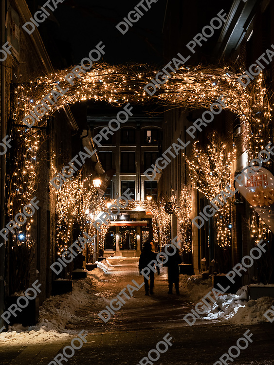 Montreal, Quebec, Canada - January 3, 2021 One unrecognizable couple walks Rue Saint Amable during winter night with viewed from Place Jacques-Cartier in Montreal Old Port