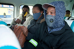 Commuters wearing masks in a taxi.