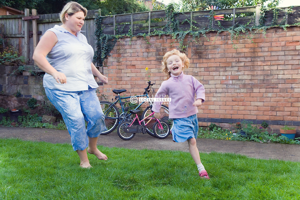 Mother and daughter playing chase  in the garden,