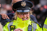 A Met Police office tries on one of the american costume police hats - The New Years Day parade passes through central London.