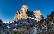 """Sunrise on War Bonnet Peak seen near Jackass Pass, Cirque of the Towers, Bridger Wilderness, Wind River Range, Bridger-Teton National Forest, Rocky Mountains, Wyoming, USA. We backpacked to Big Sandy Lake Campground (11 miles round trip with 1000 feet gain). Two hours before sunrise, I departed from Big Sandy Lake to reach Jackass Pass viewpoint for Cirque of the Towers and Lonesome Lake (6.5 miles round trip, 1860 ft gain) on the Continental Divide Trail. The Continental Divide follows the crest of the """"Winds"""". Mostly composed of granite batholiths formed deep within the earth over 1 billion years ago, the Wind River Range is one of the oldest mountain ranges in North America. These granite monoliths were uplifted, exposed by erosion, then carved by glaciers 500,000 years ago to form cirques and U-shaped valleys. This image was stitched from multiple overlapping photos."""