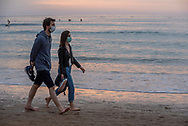 A couple, wearing protective face masks, walk on the beach at sunset. Donostia (Basque Country). May 7, 2020. Some outdoor activities have been allowed as Spain is going through the plan of downscaling following an ongoing plan to leave the confinement ordered by the Spanish government to prevent the spread of the COVID-19. (Gari Garaialde / Bostok Photo)