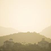 The haze catches the setting sun in the hills around Panama City, Panama.