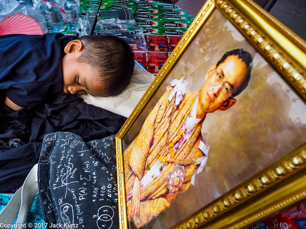 24 OCTOBER 2017 - BANGKOK, THAILAND: A child sleeps in front of a portrait of the late king, on the sidewalk of Atsadang Rd while his family waits to enter the royal cremation site. People started camping out along Atsadang Road in Bangkok near the royal cremation site on Monday. The gates won't open until Wednesday morning and the cremation isn't until Thursday night, so most people will sleep outside, on sidewalks and footpaths for three nights. Hundreds of thousands of people are expected to try to get into Sanam Luang, the site of the cremation of Bhumibol Adulyadej, the Late King of Thailand, but the site will only hold about 60,000 people. The Thai government has built replica crematoriums around Bangkok to accommodate the overflow crowds.        PHOTO BY JACK KURTZ