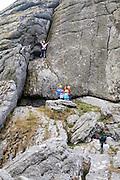 Children rock climbing on the granite tor of Haytor, Dartmoor national park, Devon, England, UK