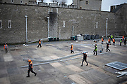 Workmen moving long girder pieces as they disassemble a temporary structure from the Tower of London on 7th January 2020 in London, England, United Kingdom. This space, just outside the walls of the tower, are used for covered corporate events at specific times of the year.