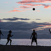 Four people playing with a ball on the beach at sunset in the village of La Preneuse.