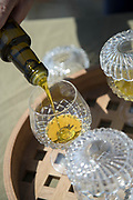 Close up of olive oil being poured into crystal glass placed on tray, Lesbos, Greece