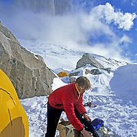 BAFFIN ISLAND, Nunavut, Canada. Jared Ogden (MR) organizes food in base camp for climb on Great Sail Peak (bkg.)