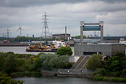 A ship passes by Central Way Pumping station, protecting homes from flooding, Thamesmere lake lake 4, next to Thamesmere leisure centre. Thamesmead, London.