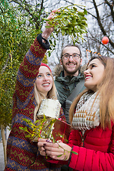 Friends with gifts and mistletoe twigs