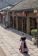 Rear view of a woman in a traditional Miao dress walking along a street in an old Chinese town, Fenghuang, Hunan Province, China