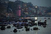 Dawn breaks over the Ganges at Varanasi as boatloads of pilgrims jostle for position.