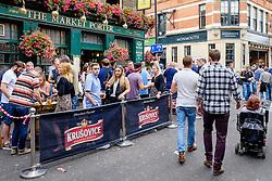 People drinking outside The Market Porter pub in Borough market, London.