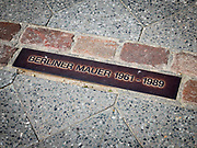 Sidewalk plaque indicating the location of the Berlin Wall and the dates that it existed