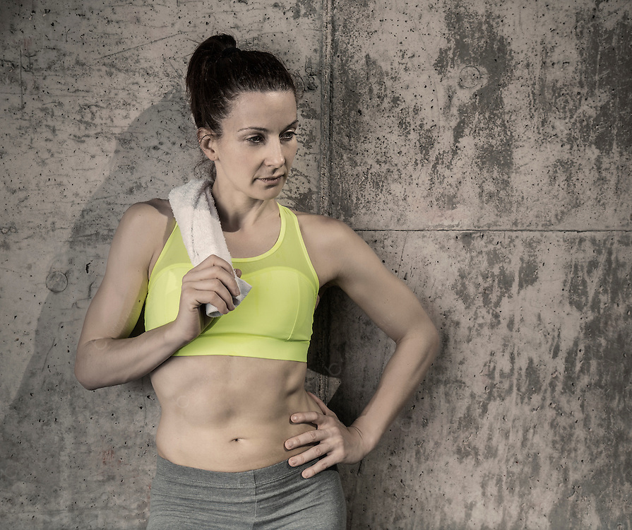 Woman in sportswear holding a towel and leaning on concrete wall