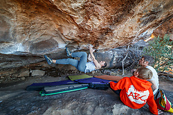 Young climber beneath overhanging boulder at Hueco Tanks State Park & Historic Site, El Paso, Texas. USA.
