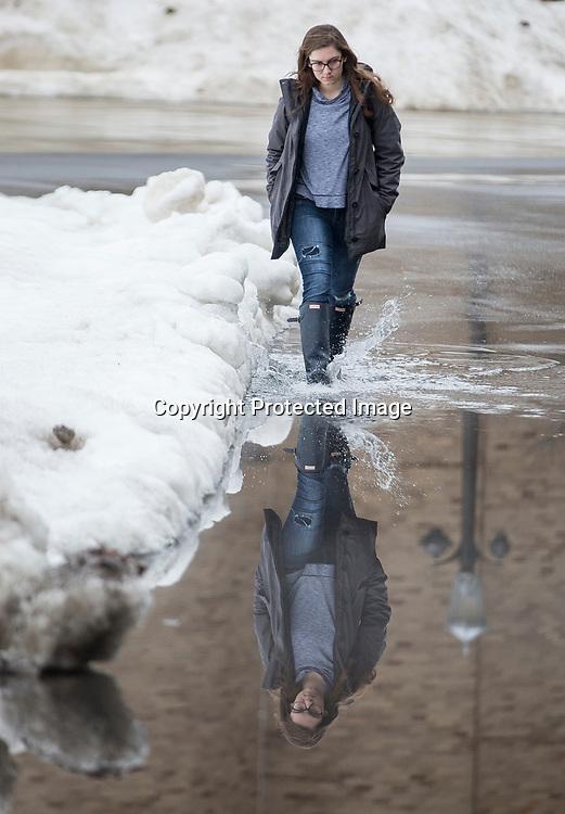 Kaleigh O'Boyle walks through a puddle near Notre Dame Stadium during a break in the rain on Monday.<br /> Tribune Photo/SANTIAGO FLORES