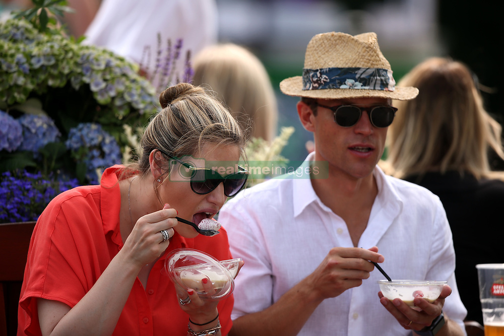 Spectators with strawberries and cream on day four of the Wimbledon Championships at the All England Lawn Tennis and Croquet Club, Wimbledon