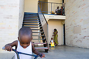 Estella Ndayikunda sweeps outside her apartment at ParkLane Terrace with her son Fledson, 2, while Frank, 3, rides his bike in Dallas, Texas on October 5, 2014. Ndayikunda lives in the unit directly below Youngor Jallah, who along with her family, have been quarantined and monitored daily for symptoms of Ebola. (Cooper Neill for The New York Times)