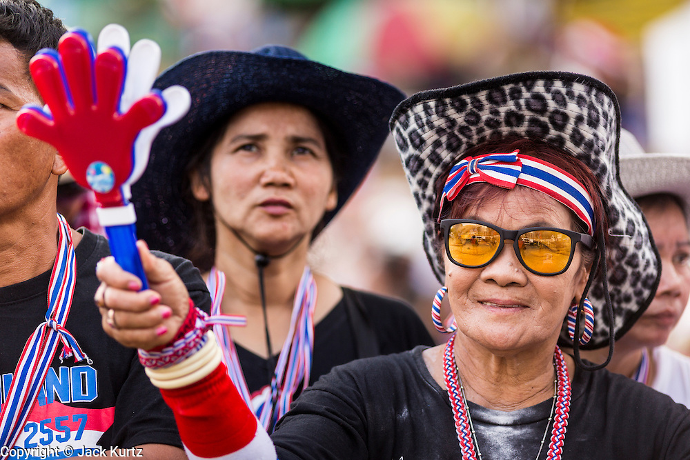 """09 MAY 2014 - BANGKOK, THAILAND:  Thai anti-government protestors listen to Suthep Thaugsuban speak in Lumpini Park Friday. Thousands of Thai anti-government protestors took to the streets of Bangkok Friday to start their """"final push"""" to bring the popularly elected of government of Yingluck Shinawatra. Yingluck has already been forced out by a recent court ruling that forced her to resign and she is facing indictment by the National Anti Corruption Commission of Thailand for alleged improprieties related to a government rice price support scheme. The protestors Friday were marching to demand that she not be allowed to return to politics. The courts have not banned her party, Pheu Thai, which has formed an interim caretaker government to govern until elections expected in July, 2014. Suthep Thaugsuban, secretary-general of the People's Democratic Reform Committee (PDRC),  said the president of the Supreme Court and the new senate speaker, who would be selected Friday, should set up an """"interim people's government and legislative assembly."""" He went onto say that if they didn't, he would.    PHOTO BY JACK KURTZ"""
