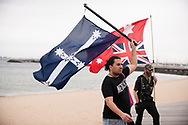 """A protesters holding a """"Eureka flag and a Australian Red Ensign flown upside down"""" on St Kilda Beach during the Sack Daniel Andrews Protest that stared in Fawkner Park. Parts of the community are looking to hold the Victorian Premier accountable for the failings of his government that led to more than 800 deaths during the Coronavirus crisis. Victoria has recorded 36 days Covid free as pressure mounts on the Premier Daniel Andrews to relax all remaining restrictions. (Photo by Michael Currie/Speed Media)"""