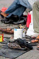 Two shoe repairmen on the streets of Saigon polish shoes.