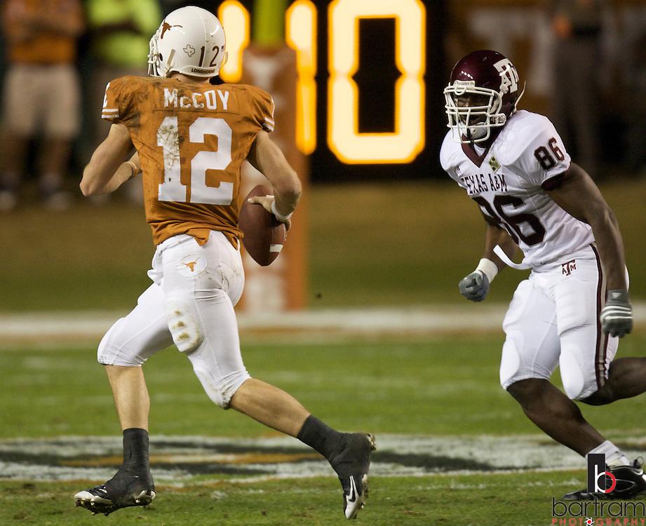 Texas quarterback Colt McCoy runs from Texas A&M defensive lineman Amos Gbunblee at Darrell K Royal Texas Memorial Stadium in Austin, Texas on Thursday, Nov. 27, 2008. The Univeristy of Texas won the game 49-9.