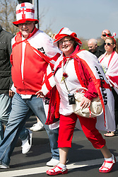 © Licensed to London News Pictures. 23/04/2015. Nottingham, UK. The Nottingham St George's parade took part today. The parade met in Forest Recreation Ground. An estimated two hundred people with trucks playing patriotic music and horses dressed in flags made their way along the streets into the City Centre. Pictured, holding hands on the route. Photo credit : Dave Warren/LNP