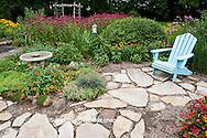 63821-206.17  Blue chair, bird bath and birdhouse in garden with  Autumn Colors Black-eyed Susans (Rudbeckia hirta 'Autumn colors'), Red and Pink Pentas (Pentas lanceolata), Butterfly Bush (Buddleia davidii), Raspberry Wine Bee Balm (Monarda didyma), Zinnias, Sedums, Dragon Wing Begonias, Marion Co. IL