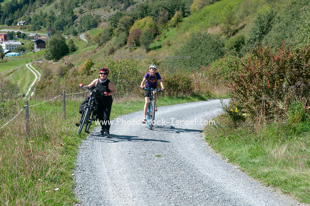 Fatigued cyclist pushes her bike up the steep climb to Guarda, Switzerlandwhile another cyclist cycles past