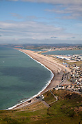 Chesil beach tombolo with housing in Chiswell in the foreground, Isle of Portland, Dorset, England, UK