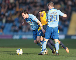 Oxford United forward David Connolly (24) is sandwiched between Burton Albion midfielder Lee Bell (7) and Burton Albion midfielder Matthew Palmer (23)  - Photo mandatory by-line: Nigel Pitts-Drake/JMP - Tel: Mobile: 07966 386802 08/03/2014 - SPORT - FOOTBALL -  Kassam Stadium - Oxford - Oxford United v Burton Albion - Sky Bet League Two