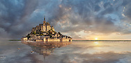 """Scenic sunset view of the tidal island  of Mont Saint Michel at high tide surrounded and its medieval abbey of Saint Michel. Normandy France.<br /> <br /> The tides vary greatly, at roughly 14 metres (46 ft) between highest and lowest water marks. Popularly nicknamed """"St. Michael in peril of the sea"""" by medieval pilgrims making their way across the flats, the mount can still pose dangers for visitors who avoid the causeway and attempt the hazardous walk across the sands from the neighbouring coast."""