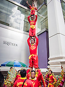 17 AUGUST 2013 - BANGKOK, THAILAND:    Members of a Dragon dance and acrobatic troupe performs at Erawan Shrine in Bangkok. The Chinese Dragon Dance began during the Han Dynasty which lasted from 206 BC to 24 AD. In those ancient days it was performed by the people of China specifically to please their ancestors and to insure sufficient rain for a plentiful crop. In this way they hoped to protect against hunger and sickness. Over time the Dragon Dance became a central feature in Chinese celebrations with different colors symbolizing different characteristics or desired features; red for excitement, green for a good harvest, yellow for a solemn empire and gold or silver for prosperity. The Dragon Dance is a well-choreographed event whose difficulty is dependent upon the performers' skill. The length of the dragon indicates just how much luck it will bring in the coming year, but a longer dragon requires more performers with great skill as an error by one can ruin the entire performance. The dragon is typically between 82 and 229 feet long. The head along can weigh as much as 31 pounds. Both strength and skill are both required in performing the Chinese Dragon Dance.        PHOTO BY JACK KURTZ