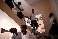 Students at Antoinette Dessalines girls school, recipients of hygiene kits donated by Lutheran World Relief, walk down a staircase at the school in St. Marc, Haiti.