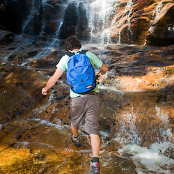 A man hiking at Arethusa Falls in Crawford Notch State Park in New Hampshire's White Mountains.