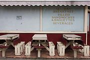 "A closed cafe that once offered all day breakfast with empty seating in central London, a victim of the UK recession. With peeling paint and unused street furniture, se see that the corner business has closed, its windows covered in white emulsion paint to render it opaque. The shop's former menu is still displayed on this window: ""Beverages and filled sandwiches & baguettes"" once sold to regular customers."