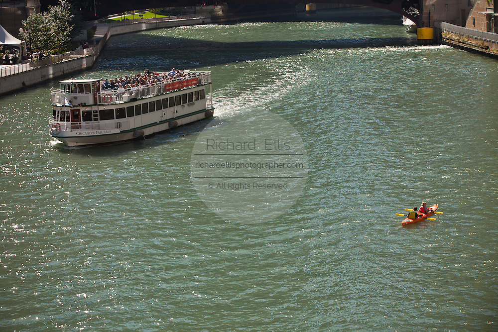 A kayak passes a sightseeing boat on the Chicago along Michigan Ave in Chicago, IL, USA.