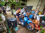 13 AUGUST 2016 - BANGKOK, THAILAND: A man washes his motorcycle while his friends eats breakfast in the Pom Mahakan slum in Bangkok. Residents of the slum have been told they must leave the fort and that their community will be torn down. The community is known for fireworks, fighting cocks and bird cages. Mahakan Fort was built in 1783 during the reign of Siamese King Rama I. It was one of 14 fortresses designed to protect Bangkok from foreign invaders. Only of two are remaining, the others have been torn down. A community developed in the fort when people started building houses and moving into it during the reign of King Rama V (1868-1910). The land was expropriated by Bangkok city government in 1992, but the people living in the fort refused to move. In 2004 courts ruled against the residents and said the city could take the land. Eviction notices have been posted in the community but most residents have refused to move. Residents think Bangkok city officials will start evictions around August 15, but there has not been any official word from the city.      PHOTO BY JACK KURTZ