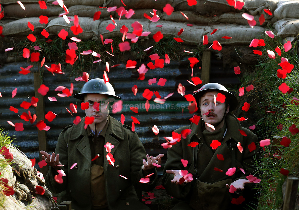 Poppies fall on actors James Dutton(L) and Sam Duncane during the launch of the Poppyscotland fundraising challenge The 1918 Poppy Pledge. They are seen in a recreated First World War trench at Pollok Country Park in Glasgow.