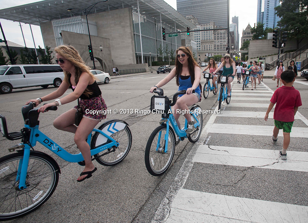 People ride Divvy bikes on Monday, August. 19, 2013 in Chicago, Illinois. Divvy is a bicycle sharing system that launched in Chicago on June 28, 2013 with 750 bikes at 75 stations spanning from the Loop north to Fullerton Ave, west to Damen Ave, and south to 23rd St. The system is planned to grow to 3000 bikes at 300 stations by August 2013 and 4,000 bicycles at 400 stations by Spring 2014.(Photo by Ringo Chiu/PHOTOFORMULA.com)