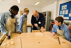 Woodwork teacher showing students how to saw wood in Design technology lesson,