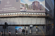 Pedestrians and passers-by walk beneath a large hoarding featuring new housing, on 9th December 2016, on Borough High Street, central London, England.