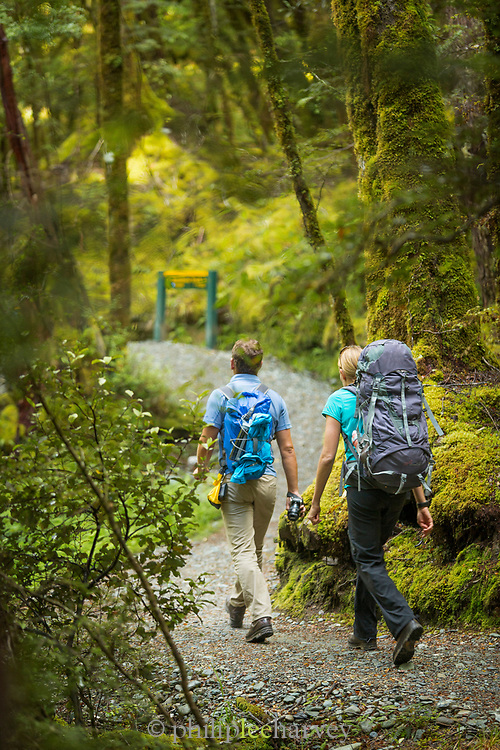 Rear view of two hikers hiking along the trail near the beginning of the Routeburn Track from the Routeburn Shelter, South Island, New Zealand